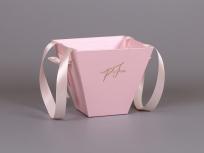 """<p><strong><em>Материал:</em></strong>картон,<em>дизайнерская бумага маджестик (розовый лепесток), люверсы металлические и ручка лента атласная с 2-мя бантиками(входят в стоимость)</em></p> <p><em><strong>Технология:</strong>вырубка картона, монтаж ручек</em></p> <p><em><strong>Размер, мм.:</strong>200х200 высота 180 мм</em></p> <p><strong><em>Примерная стоимость, руб.:</em></strong></p> <p>оклейка пленкой цветной оракал(с оклейкой внутри) - от 475</p> <p>оклейка бумагой маджестик, сирио(с оклейкой внутри) от - 394 (вариант на фото)</p> <p>оклейка крафт бумагой (с оклейкой внутри) от - 311</p> <p><em><em><em><em><em><em><em><em><em><em><strong><em><a title=""""KP na trapecii"""" href=""""http://estetis.ru/files/doc/KP%20na%20trapecii.pdf"""" target=""""_blank"""">Подробно про коробки - трапеции для цветов</a></em></strong></em></em></em></em></em></em></em></em></em></em></p>"""